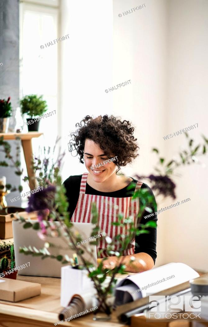 Stock Photo: Smiling young woman using laptop in a small shop with plants.