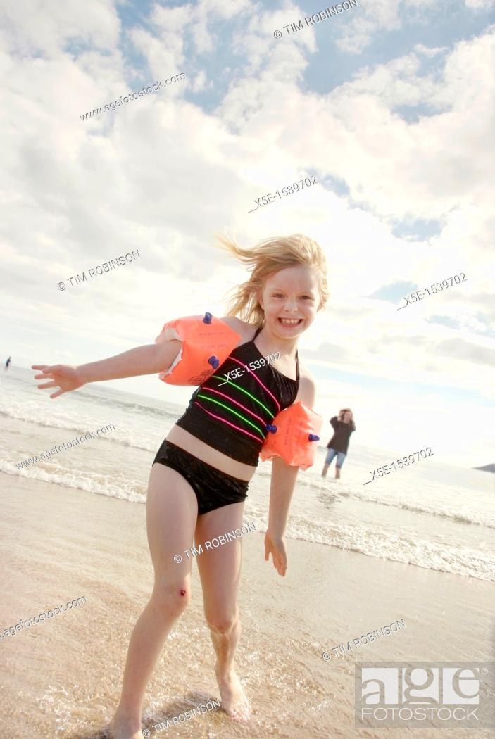Stock Photo: 8 year girl wearing flotation armbands standing on beach smiling.
