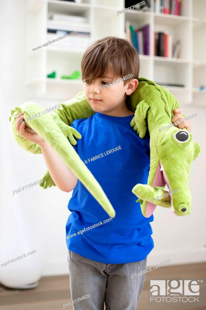 Stock Photo: Boy playing with animals toys.