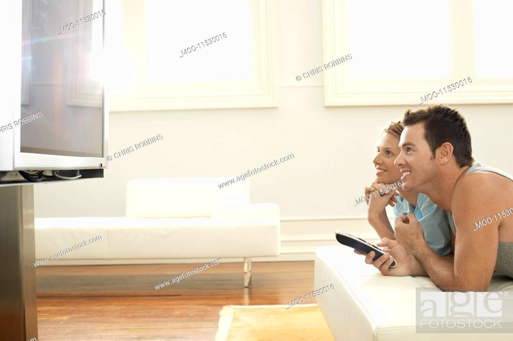 Stock Photo: Couple lying on bed watching plasma TV together side view.