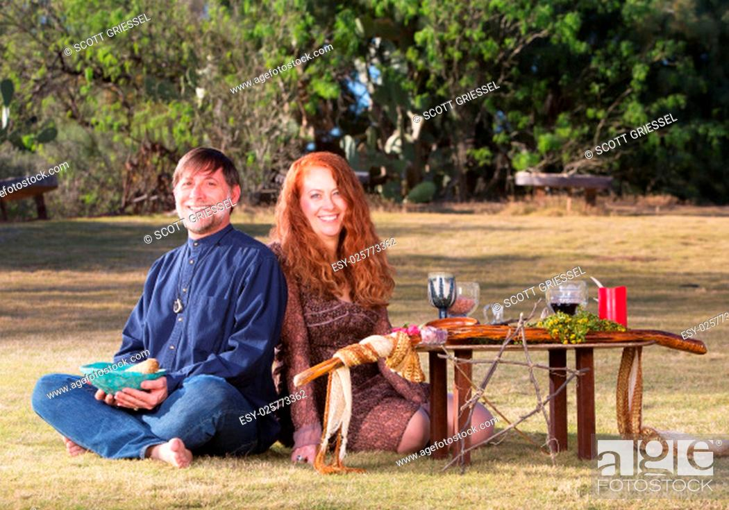 Stock Photo: Happy pagan couple at altar with candles and goblets.
