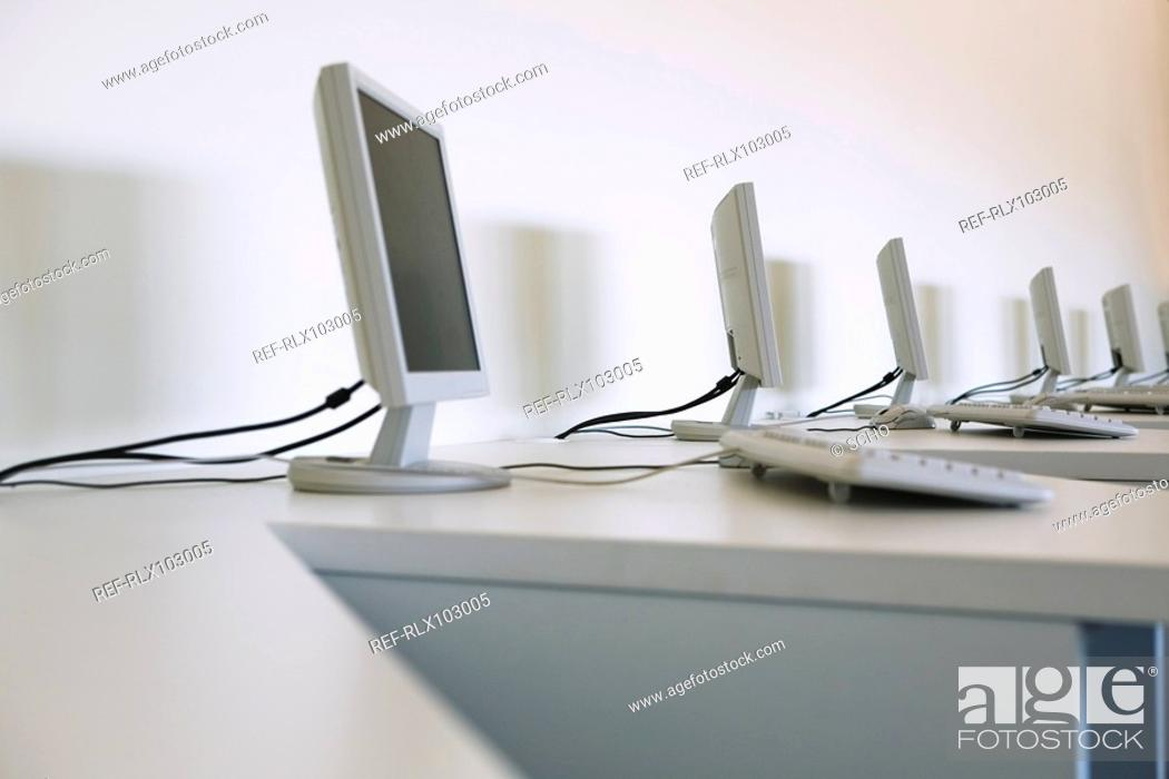 Stock Photo: Row of computer monitors and keyboards in classroom.