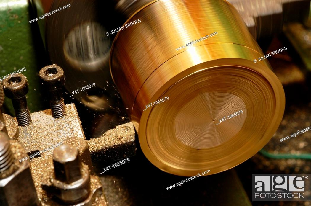 Stock Photo: turning a piece of brass bar on a lathe using a knife turning tool.