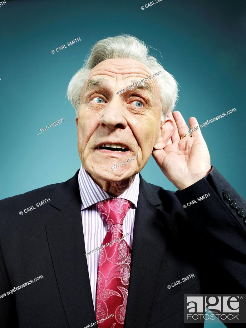 Stock Photo: A senior man with his hand behind his ear.