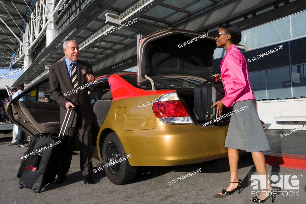 Stock Photo: Side profile of a businesswoman loading her suitcase on a car trunk with a businessman standing in front of her.