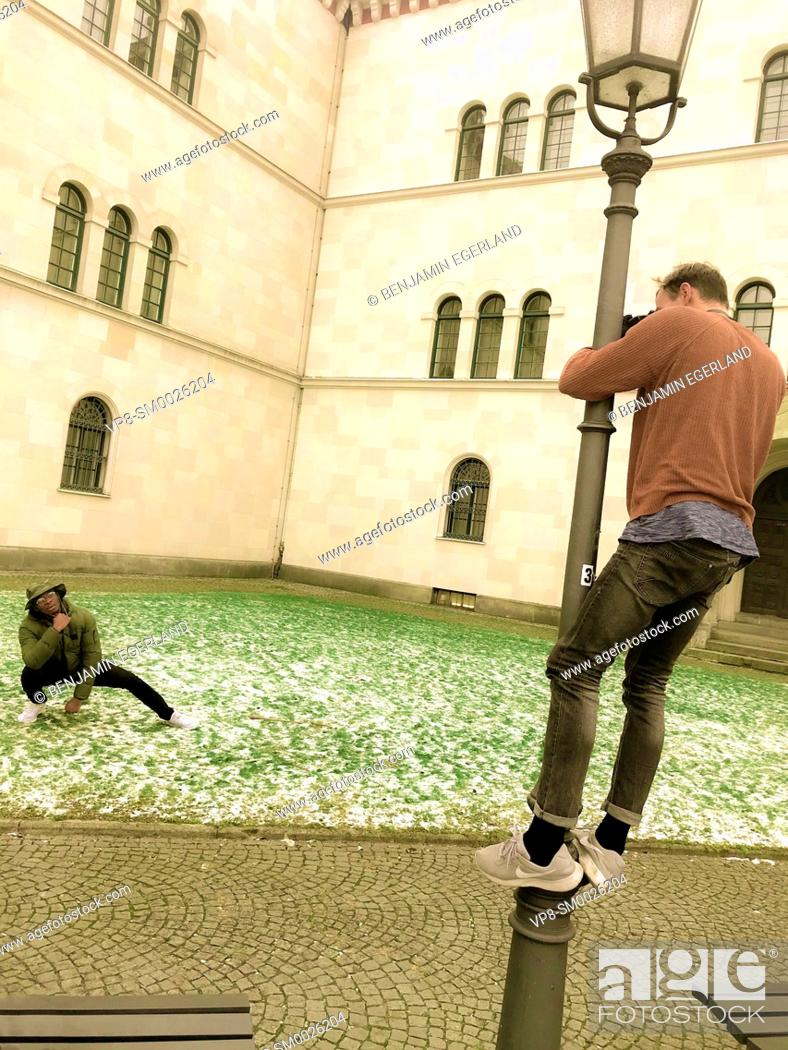 Imagen: motivated photographer climbing on street lamp to photograph male model from above, at street in city Munich, Germany.