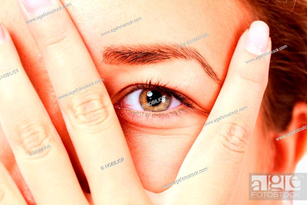Stock Photo: girl looking between her fingers.