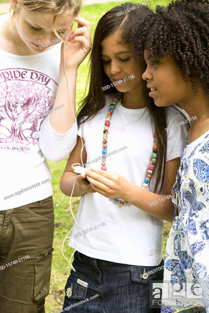Stock Photo: Close-up of two girls listening to music with another girl standing beside them.