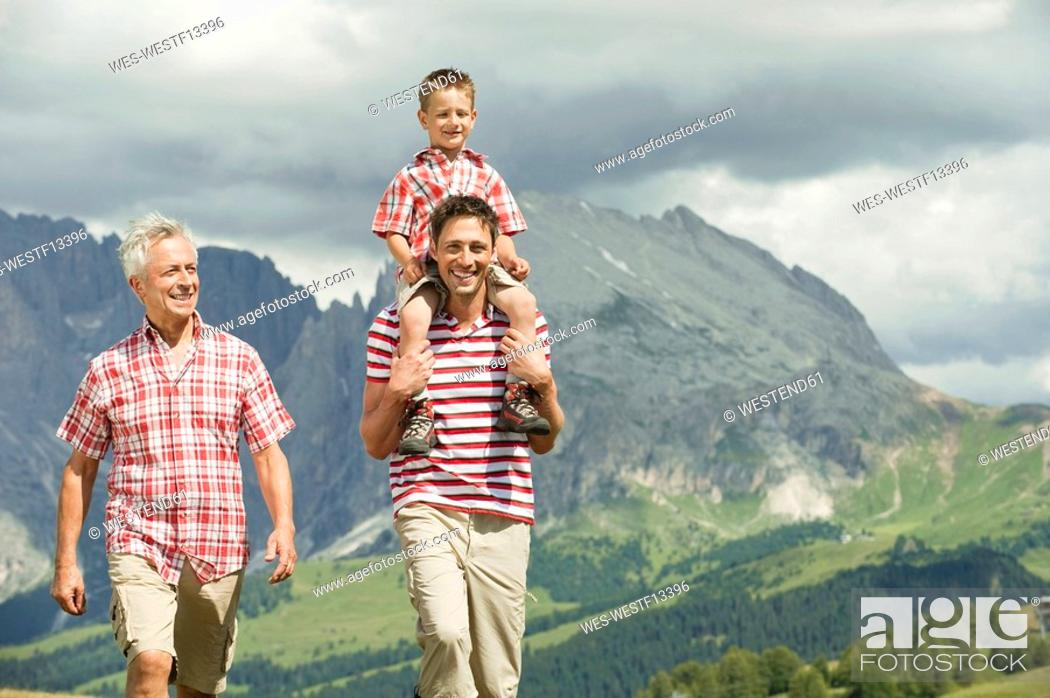 Stock Photo: Italy, Seiseralm, Grandfather, Father and son 6-7 walking in meadow, smiling, portrait.