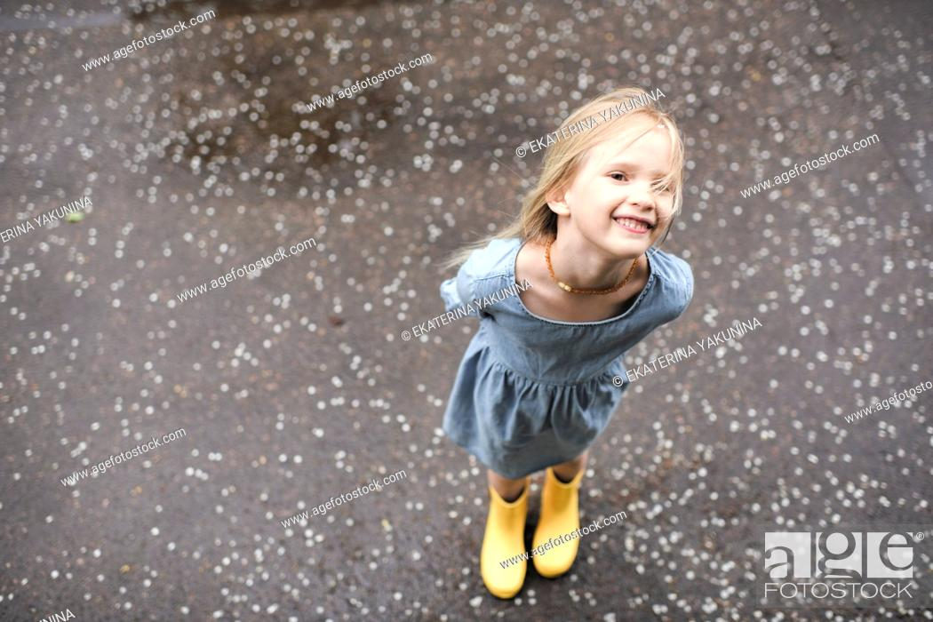 Stock Photo: Girl wearing blue dress and rubber boots.
