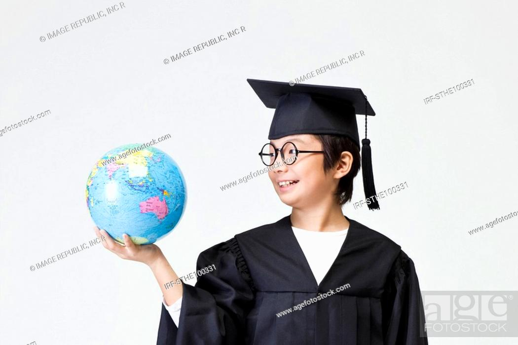 Stock Photo: boy in graduation gown.
