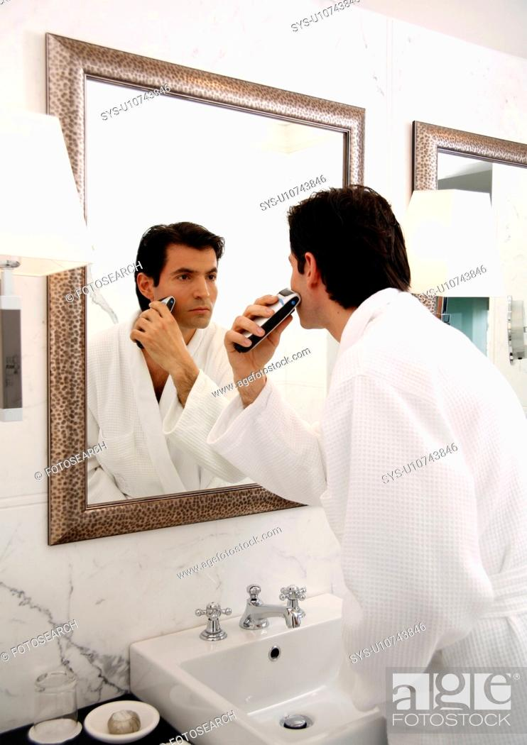 Stock Photo: Man shaving in the bathroom mirror.