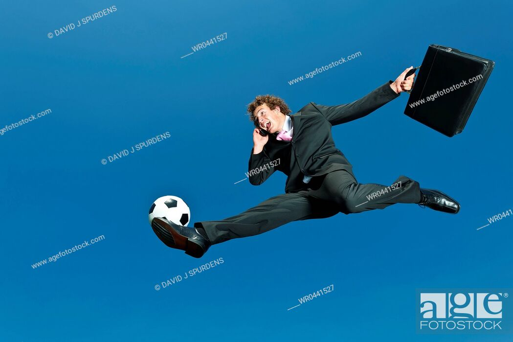 Stock Photo: A soccer playing businessman volleys ball whilst on cellphone.