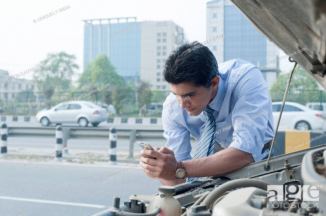 Imagen: Businessman leaning on a broken down car and using mobile phone, Gurgaon, Haryana, India.