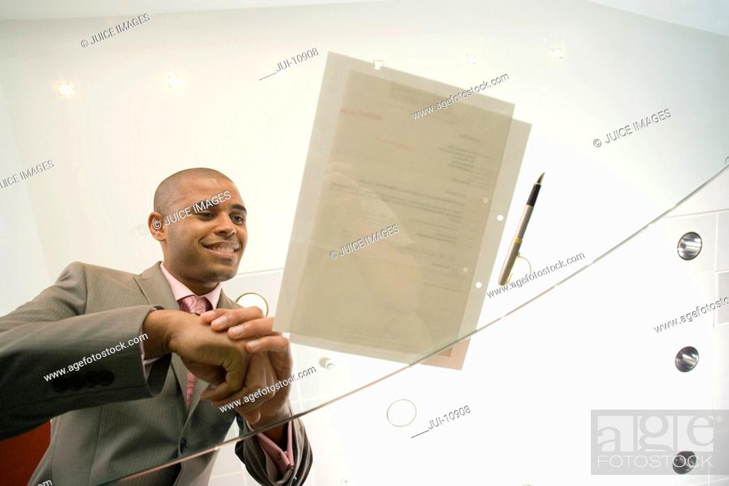 Stock Photo: Businessman by pen and paperwork on glass table, smiling, low angle view through glass.