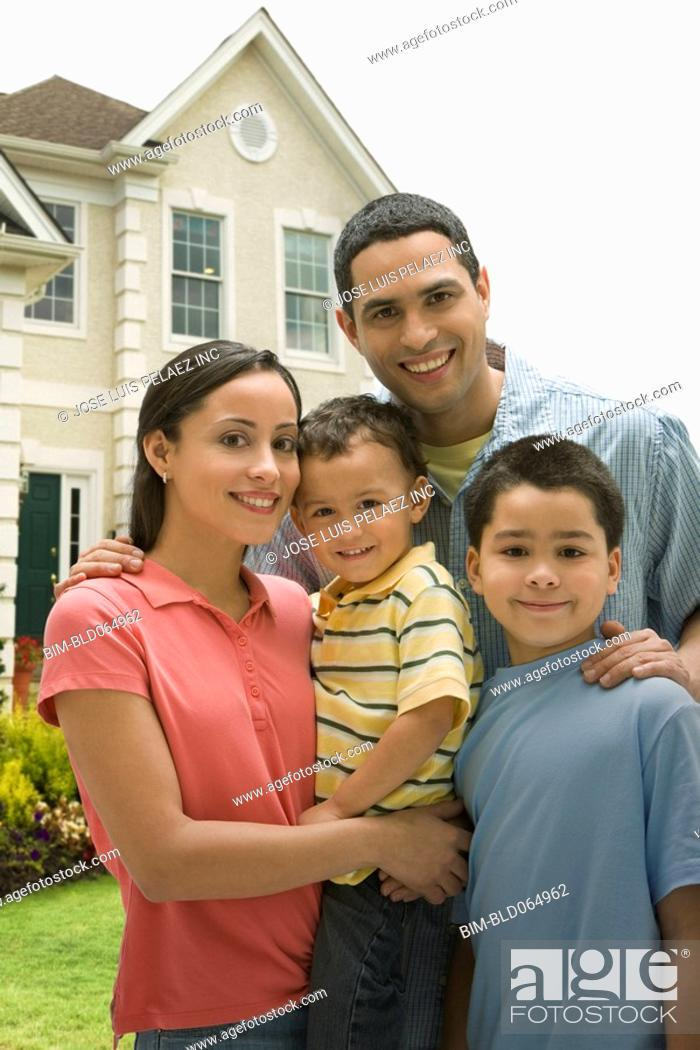 Stock Photo: Hispanic family posing in front yard of home.