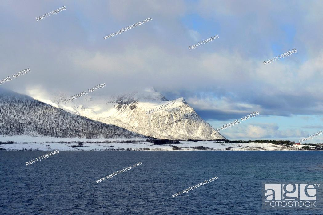 Stock Photo: The Risøysound and the Vesterålen Island Andoya with snow-white mountains surrounded by clouds, 10 March 2017   usage worldwide.