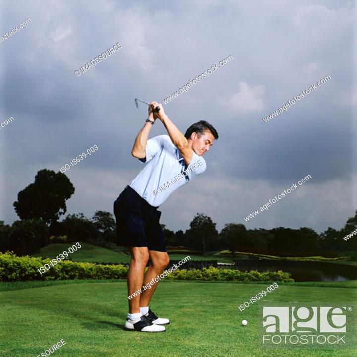 Stock Photo: Man swinging golf club.