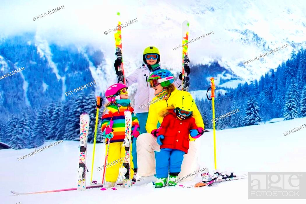 Stock Photo: Mother and children skiing in the mountains. Active mom and three kids with safety helmet, goggles and poles. Ski lesson for young children.