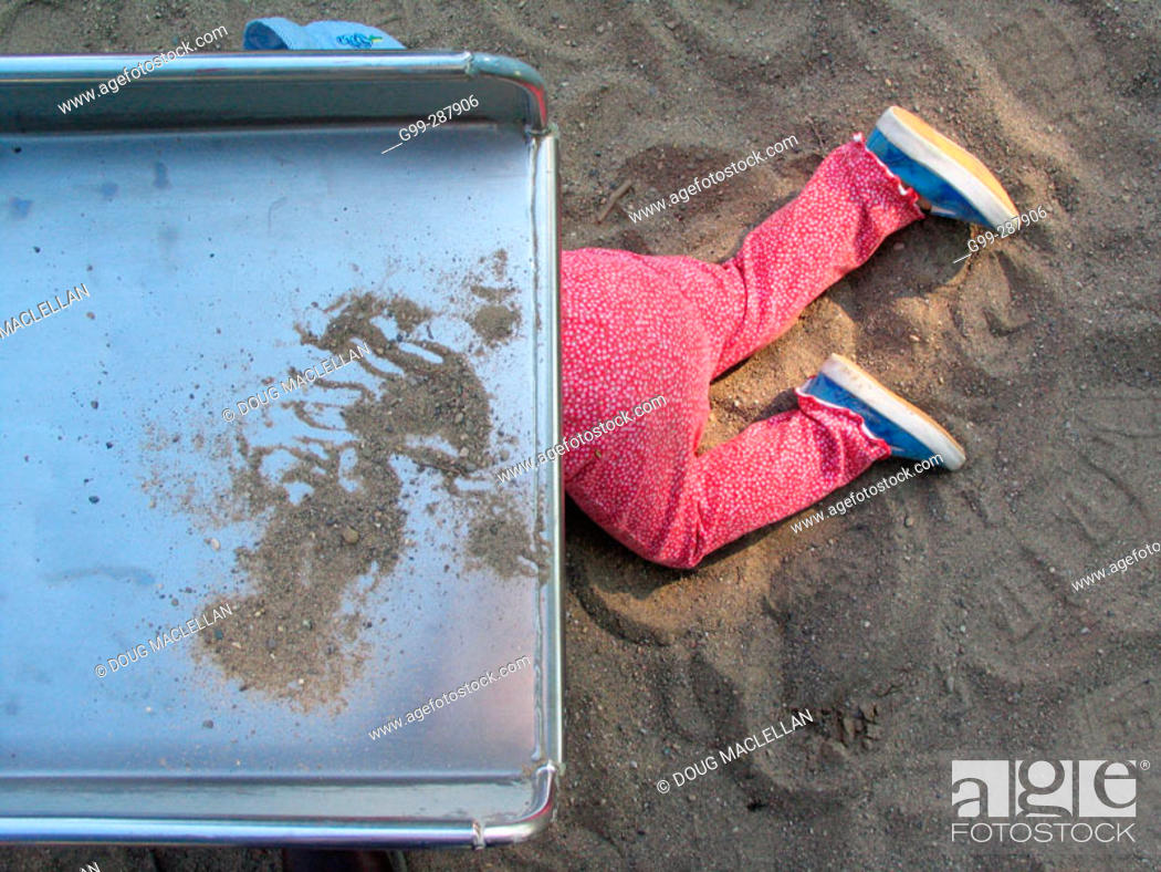 Stock Photo: 18 month old toddler playing under slide at playground.