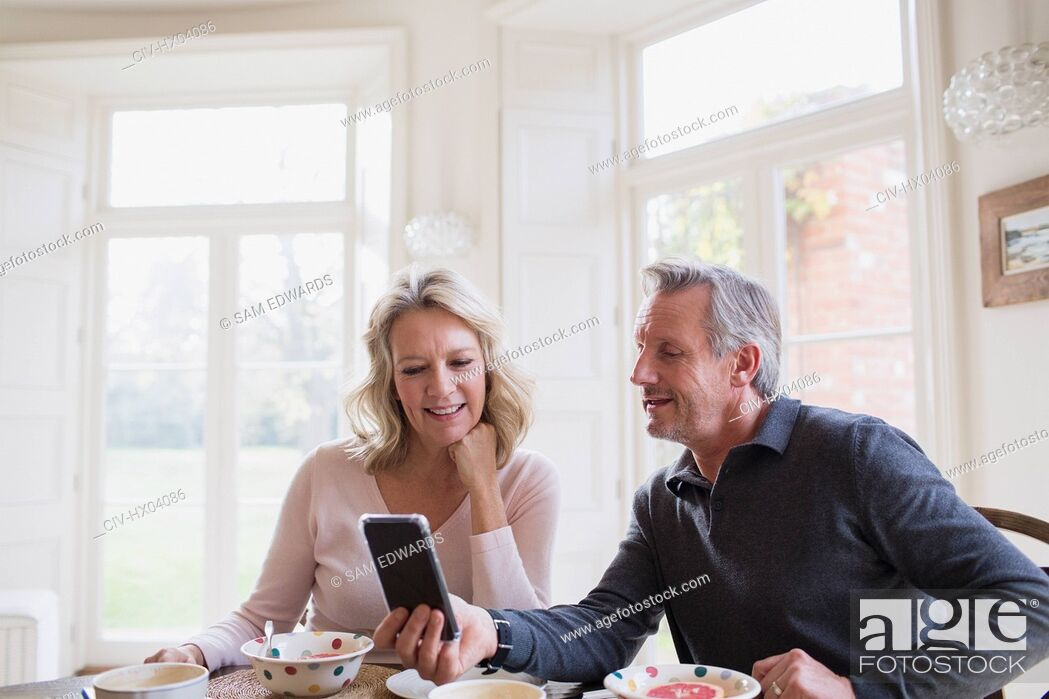 Stock Photo: Mature couple using smart phone at breakfast table.