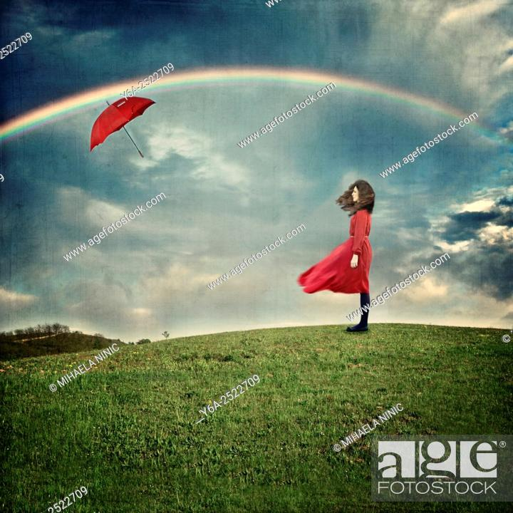 Stock Photo: Dreamy image of young woman in red dress standing on hill.