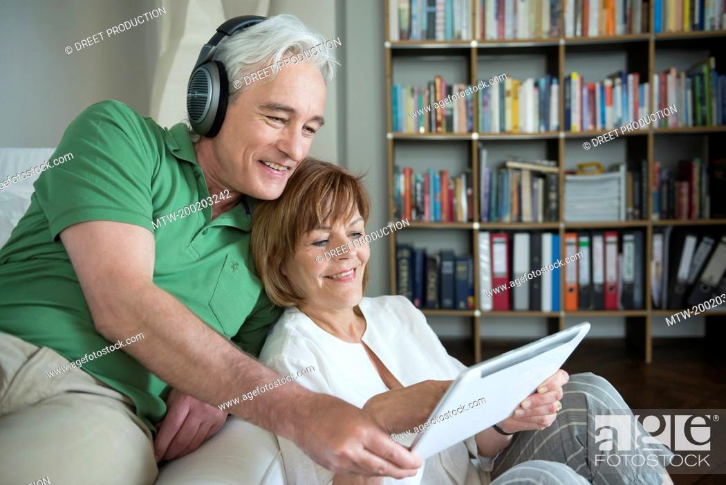 Imagen: Couple using digital tablet while man with headset, smiling.