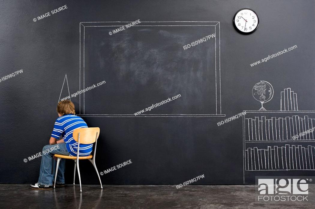 Stock Photo: A boy sat in a corner with a chalk dunce cap.
