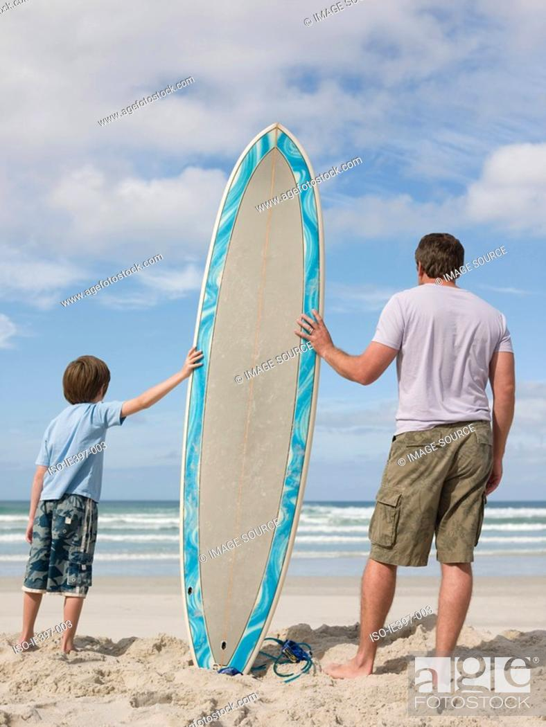 Stock Photo: Father and son with surfboard.