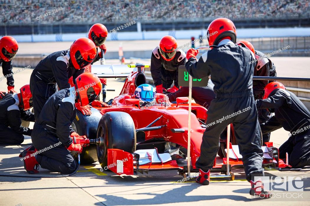 Stock Photo: Pit crew working on formula one race car in pit lane.