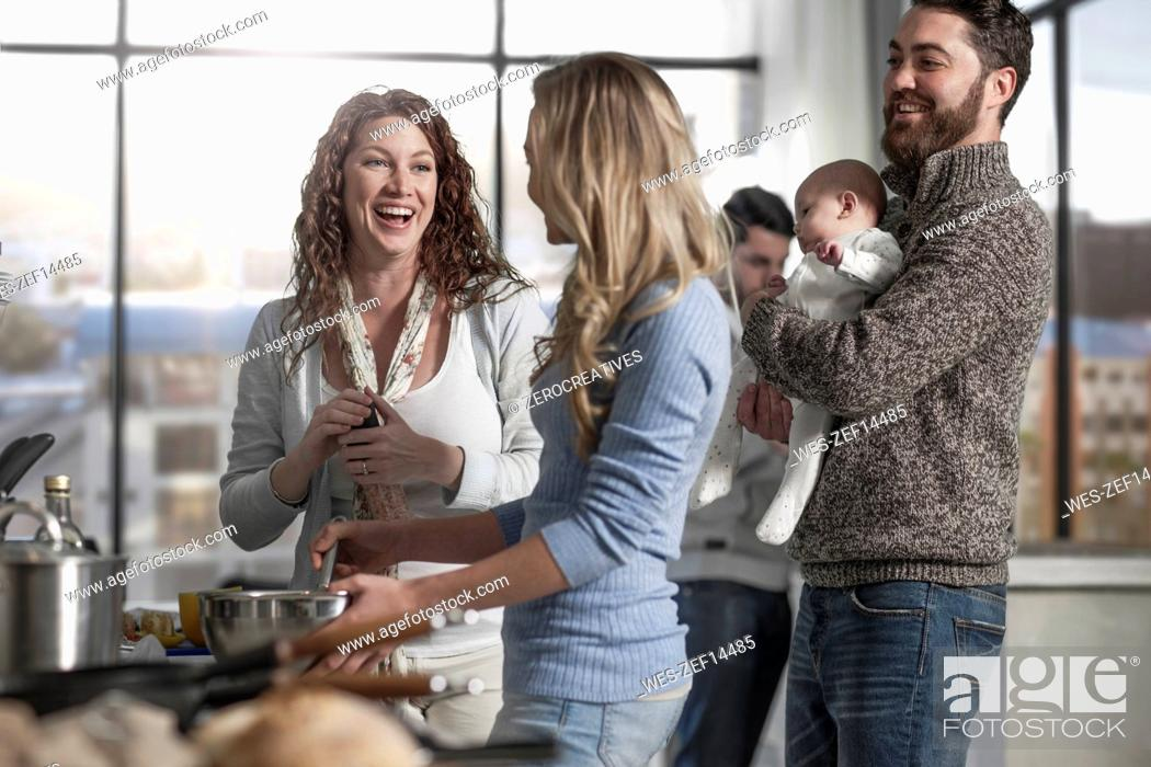 Stock Photo: Family and friends preparing meal in kitchen.