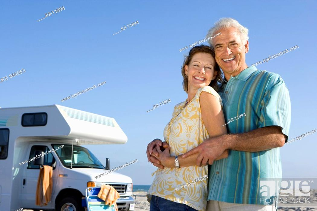 Stock Photo: Mature couple by motor home on beach, smiling, portrait, low angle view.