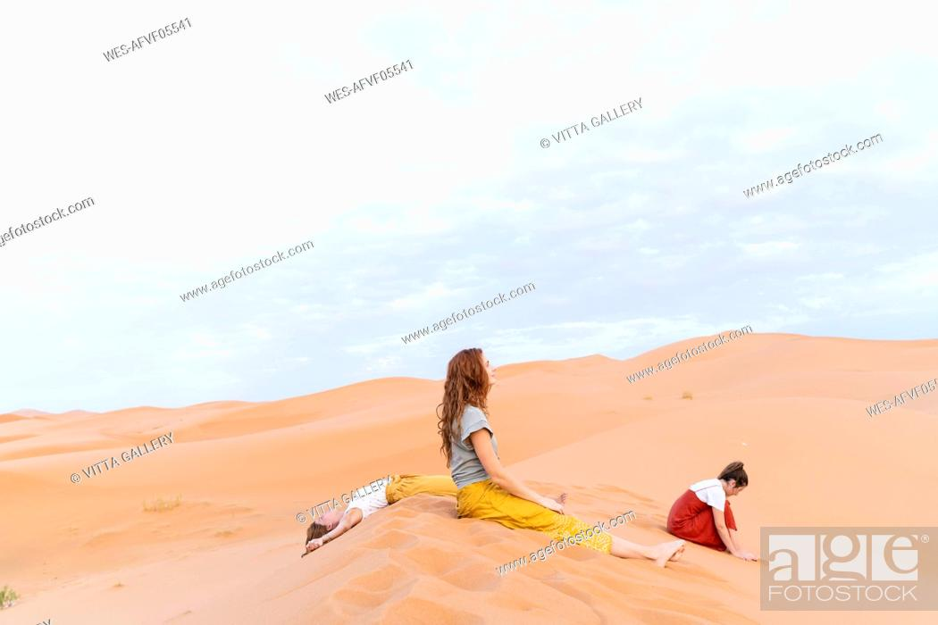 Stock Photo: Three young women resting in sand dune in Sahara Desert, Merzouga, Morocco.
