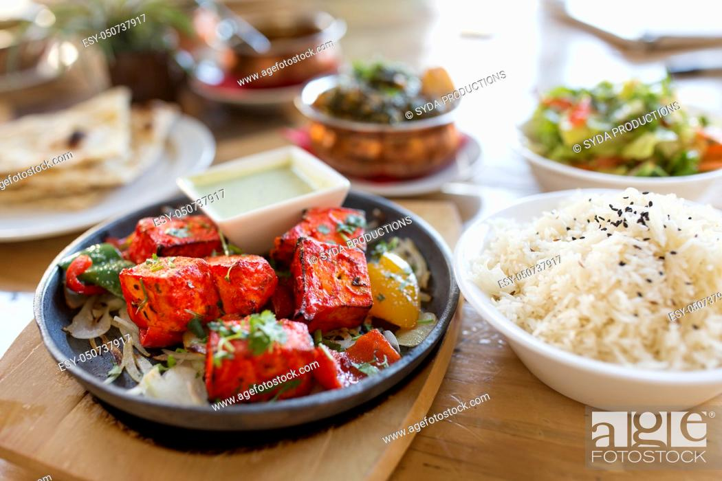 Stock Photo: close up of paneer tikka dish with sauce on table.