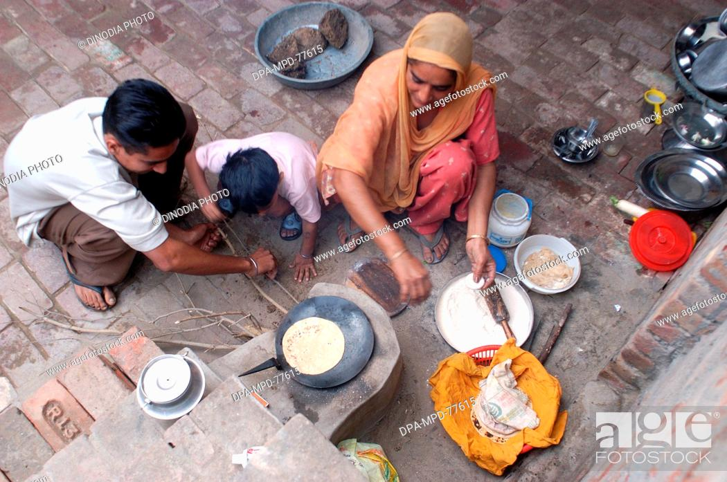 Stock Photo: A Punjaban (word used to describe Punjabi woman) making rotis on the clay choolah in the open kitchen at home while her sons trying to light the fire ; in Doulo.