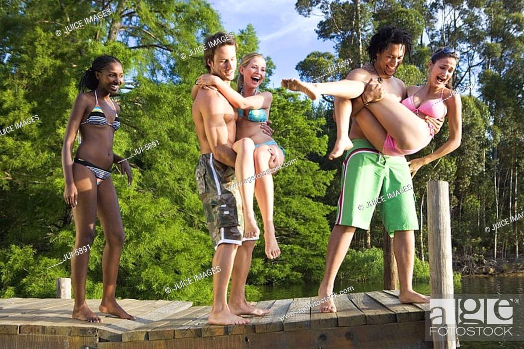Stock Photo: Two young men throwing female friends, in bikinis, from jetty into lake, laughing.