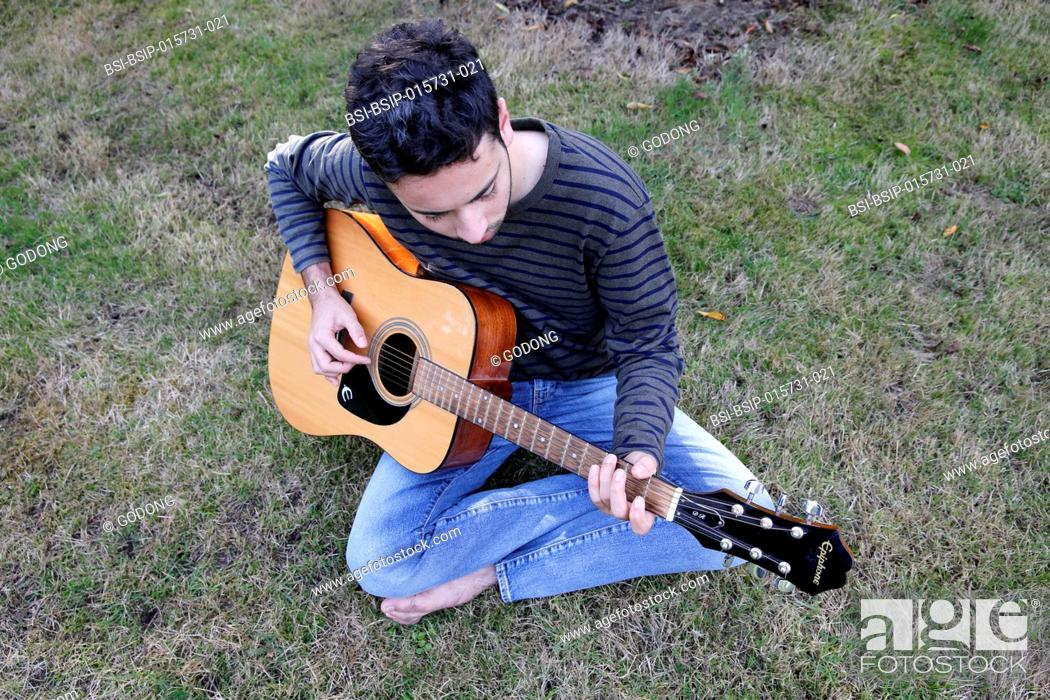 Imagen: Young man playing a guitar in a garden. France.