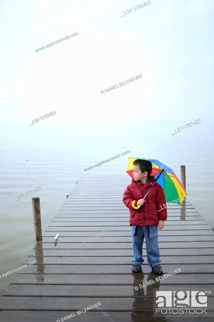 Stock Photo: boy with multicoloured umbrella under the raoin by a lake, Albufera de Valencia Nature reserve, Valencia, Spain.