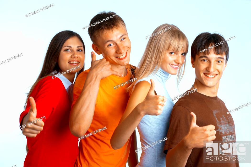 Stock Photo: Four young people on white background laughing and giving the thumbs-up sign.
