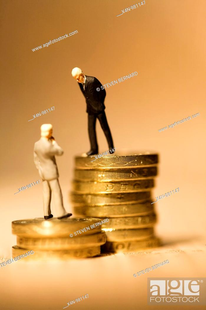 Stock Photo: Miniature businessmen standing on coins on financial newspaper  This photo illustrates the vast gap in wages within companies  Senior executives earnings have.