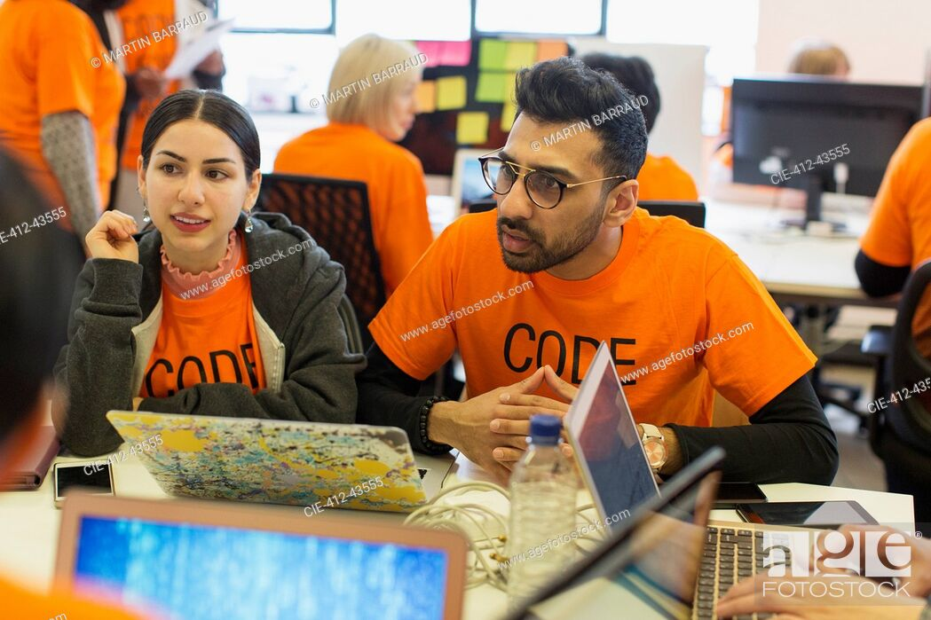 Stock Photo: Hackers coding for charity at hackathon.