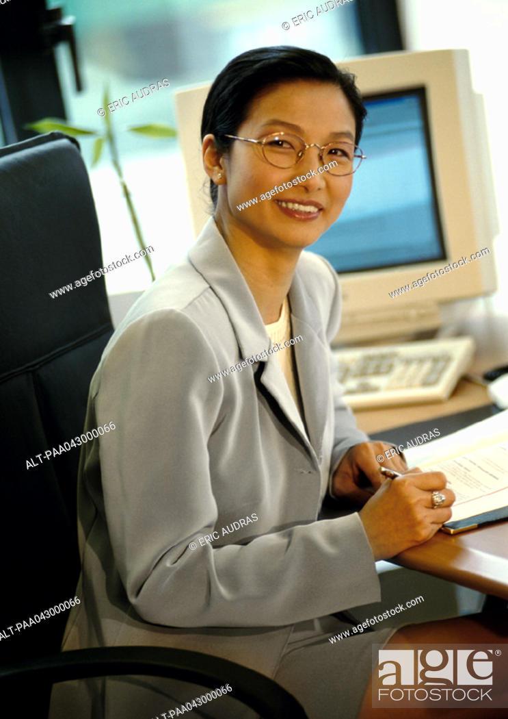 Stock Photo: Businesswoman sitting at desk, smiling at camera.