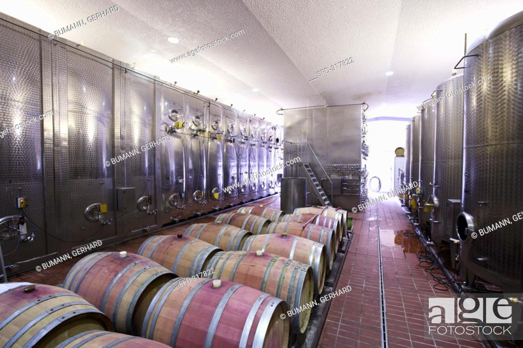Stock Photo: Stainless steel tanks and wooden barrels at a winery.