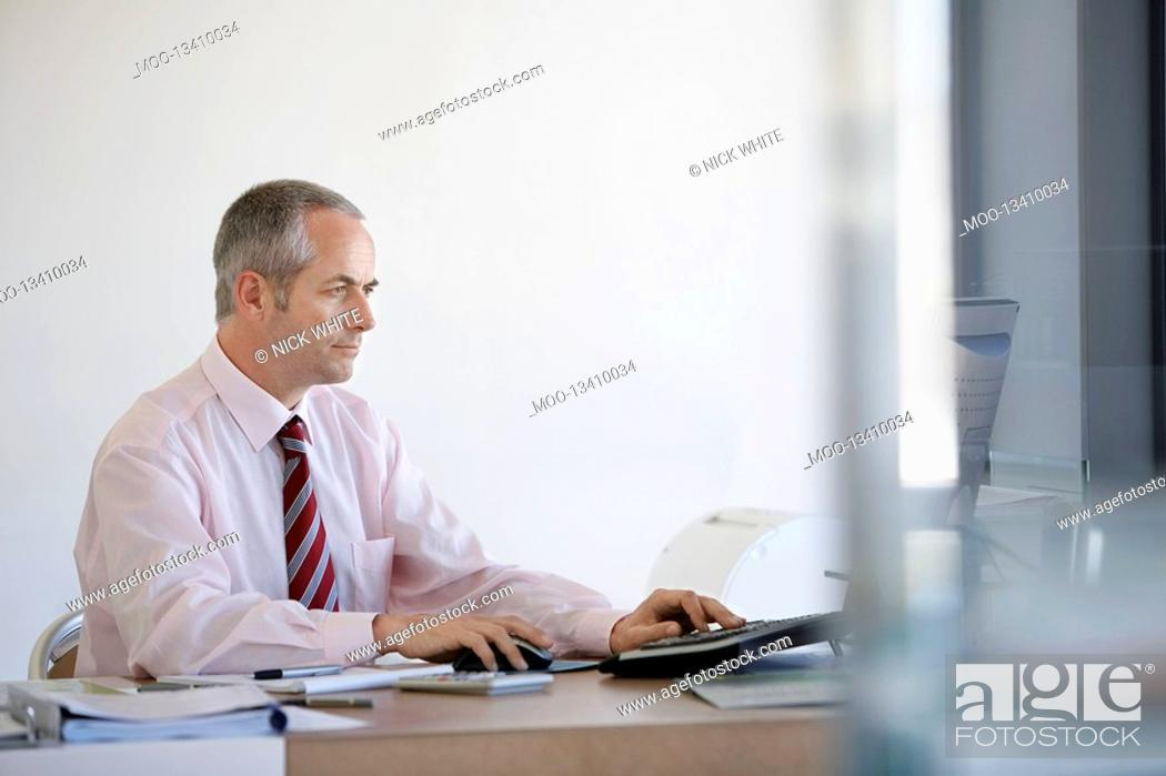 Stock Photo: Businessman sitting at desk in office using computer.