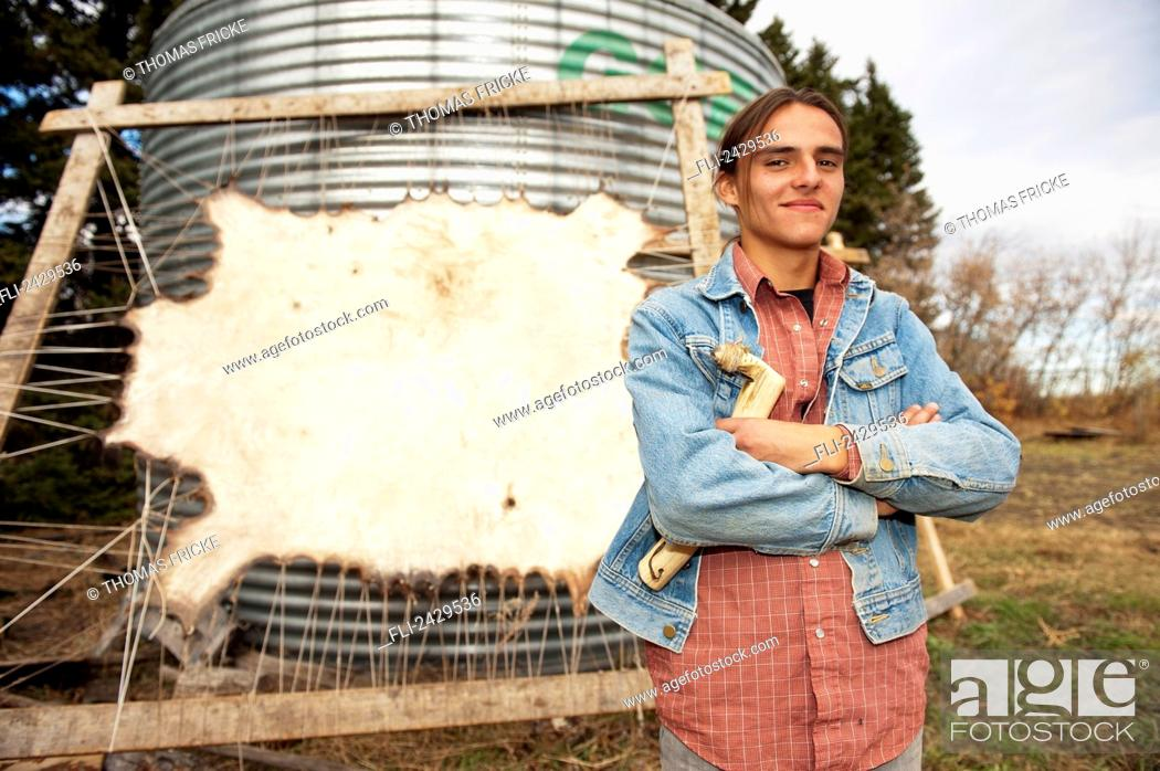 Stock Photo: Native American boy standing in front of a stretched buffalo hide; Rossburn, Manitoba, Canada.