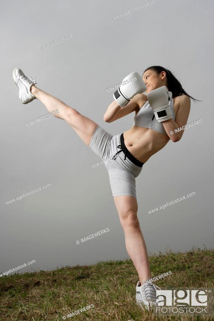 Stock Photo: View of a young woman kicking.
