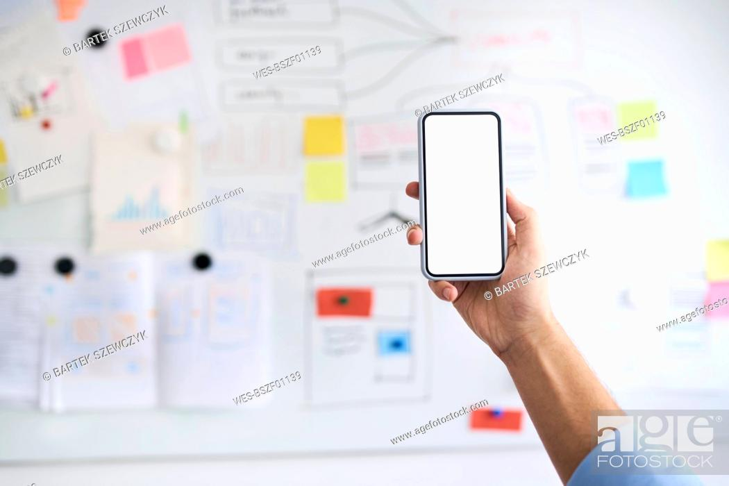 Imagen: Male hand holding aloft a smartphone in front of a whiteboard.