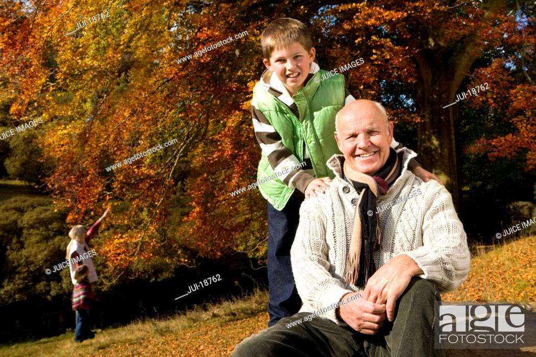 Stock Photo: Portrait of grandfather and grandson in woods with autumn leaves.