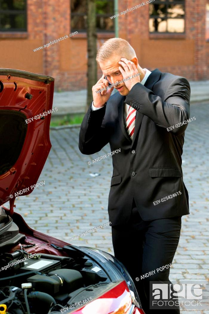 Stock Photo: Stressed Young Man Calling On Cellphone For Service With His Breakdown Car.