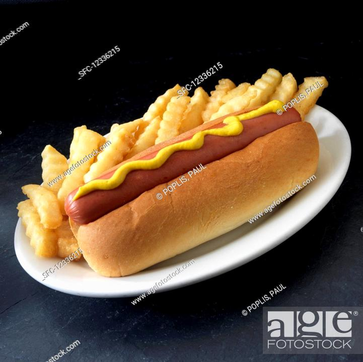 Stock Photo: Hot dog with yellow mustard and french fried potatoes.